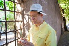 Caucasian man i tidigt femtiotal genom att använda smartphonen vid italiensk viney arkivbild
