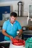 Caucasian man in the kitchen slicing watermelon Royalty Free Stock Image