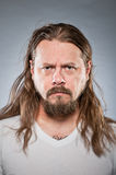 Caucasian Man With Long Hair. A Caucasian man in his 30's looking displeased royalty free stock photography
