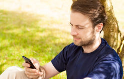 Caucasian man looking on a mobile phone outdoor Royalty Free Stock Photography