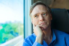 Caucasian man looking out train window, thinking, leaning on han Royalty Free Stock Image
