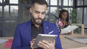 Caucasian man looking pictures on tablet in the foreground while African American female designer checking papers in the. Caucasian man looking pictures on a stock video