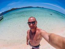 Caucasian man makes selfie at the Flores Taka Makassar Beach royalty free stock image