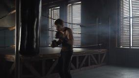 Caucasian man med boxninghandskar som stansar påsen i industriell idrottshall nära boxningsringen arkivfilmer