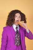 Caucasian man med den afro bärande liladräkten som äter smörgåsen royaltyfria foton