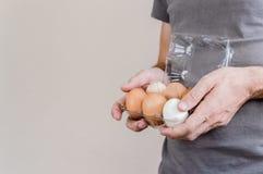 Caucasian man med den gråa tshirten som mycket rymmer en plast- äggask av fega ägg arkivbilder