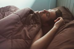 Caucasian man napping in bed in the morning. Soft light of sun Stock Photos