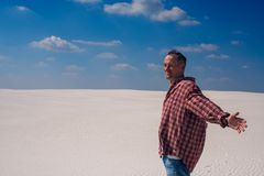 Caucasian man with open arms, stands in desert royalty free stock photo