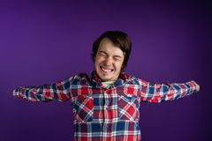 Caucasian man in plaid shirt stretch oneself on purple background.  Stock Photography