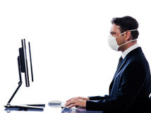 Caucasian Man portrait with computer wearing mask Royalty Free Stock Photography