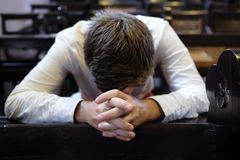 Caucasian man praying in church. He has problems and ask God for help royalty free stock photography