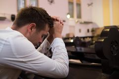 Caucasian man praying in church. He has problems and ask God for help royalty free stock photo