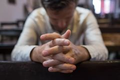 Caucasian man praying in church. He has problems and ask God for help. Concept of religion faith royalty free stock photography
