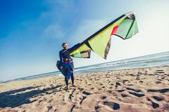 Caucasian man professional surfer standing on the sandy beach with his kite and board. Handsome Caucasian man professional surfer standing on the sandy beach Stock Photos