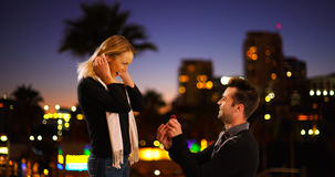 Caucasian man proposes to his girlfriend at night outdoors Stock Photo