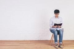 Caucasian man reading book interior Royalty Free Stock Image