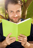 Caucasian man reading a book in a park. Portrait of happy smiling forty years old caucasian man reading a book outdoor in a park while sitting by a tree during a Royalty Free Stock Photography