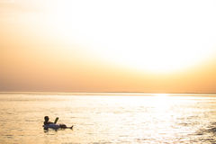 Caucasian man reads a book floating on the sunset in the ocean water. Summer vocation. Caucasian man reads a book floating on the sunset in the ocean water Royalty Free Stock Photography