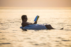 Caucasian man reads a book floating on the sunset in the ocean water. Summer vocation. Caucasian man reads a book floating on the sunset in the ocean water Stock Photography