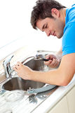 Caucasian man repairing a kitchen sink Stock Images