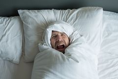 Caucasian man rolled in white blanket. royalty free stock photos