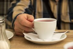 A caucasian man`s hand holds a white cup with red herbal tea. Wooden table. Peace and tranquility during the break. Ring on hand. Stock Photos