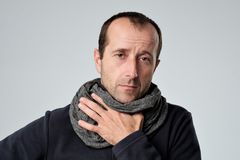 Caucasian man in scarf with headache and sore throat has cold Stock Photo