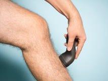 Caucasian man shaving hair from legs. Close up of young Caucasian man shaving hair from legs royalty free stock image
