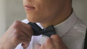 Caucasian man with a short haircut corrects a bow tie near the window in the studio. The groom in a white shirt and stock video footage