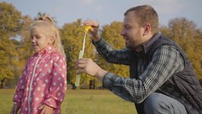 Caucasian man showing his little daughter how to blow soap bubbles. Father entertaining cute blonde girl dressed in pink. Dotted jacket in the autumn park stock footage