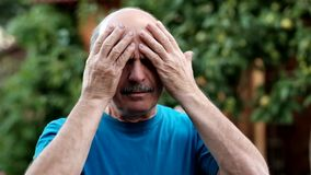 Caucasian man showing how much his head hurts, looking miserable and exhausted standing outdoor in garden