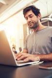 Caucasian man sitting in coffee shop using laptop Stock Photos