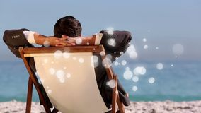caucasian man sitting on deck chair in front of sea with bubble light animation