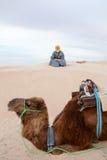 Caucasian man sitting on sand dune in desert Stock Images