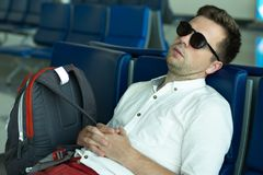 Caucasian man is sleeping in lounge area at the airport. He is tired after long trip Stock Photography