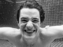 Caucasian man smiling underwater in swimming pool grayscale Royalty Free Stock Image