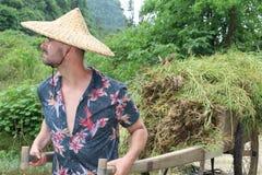 Caucasian man som arbetar i asiatisk lantgård arkivfoton