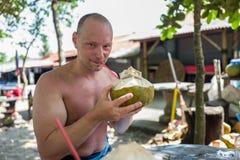 Caucasian man som dricker från kokosnöten på Echo Beach, Bali Arkivfoton