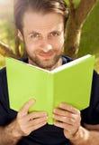 Caucasian man som läser en bok i en parkera Royaltyfri Fotografi
