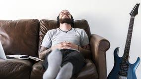Caucasian man som tar ett avbrott från arbete, genom att lyssna till begreppet för musikspänningslättnad fotografering för bildbyråer