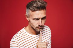 Caucasian man in striped t-shirt holding index finger on lips wi. Th angry look isolated over red background royalty free stock photography