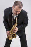 Caucasian Man in Suite Playing the Saxophone. Posing Against White Stock Photos