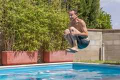Caucasian man takes a bomb dive in the pool stock photography