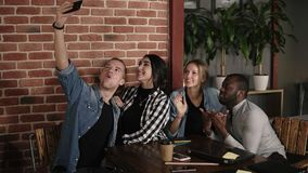 Caucasian man taking group selfie at meeting with diverse friends in coffeeshop or workplace, multiracial positive young stock video footage