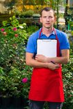 Caucasian man is taking notes in a flower greenhouse Stock Photo