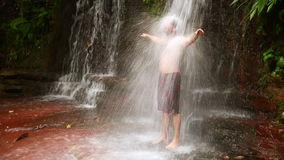 Caucasian man taking a shower in waterfall stock video footage
