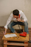 A caucasian man is talking on the phone. A caucasian man in casual clothes is talking on the phone and writing something down Royalty Free Stock Image
