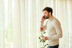Caucasian man, telefon och blomma Arkivbilder