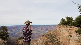 Man Tourist Talking On The Radio Traveling The Grand Canyon. Caucasian man tourist in a hat, talking on the portable radio transmitter, traveling to the national stock video