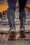 Man trains in running on the stairs. Track and field runner in sport uniform training outdoor. athlete, below view. step exercises royalty free stock image